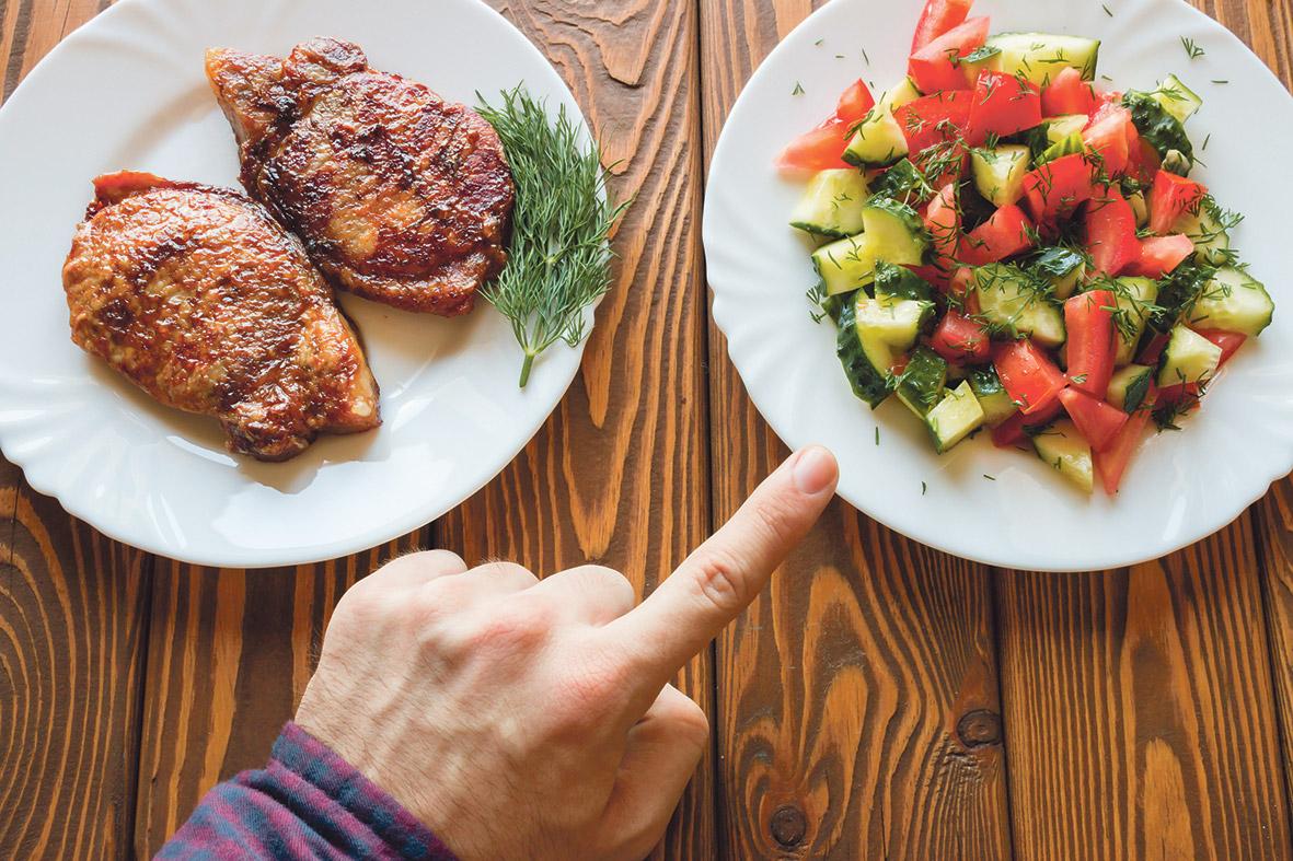 Ein Teller mit Fleisch und einer mit Gemüse. Eine Hand zeigt auf den Gemüseteller. Thema: Flexitarismus