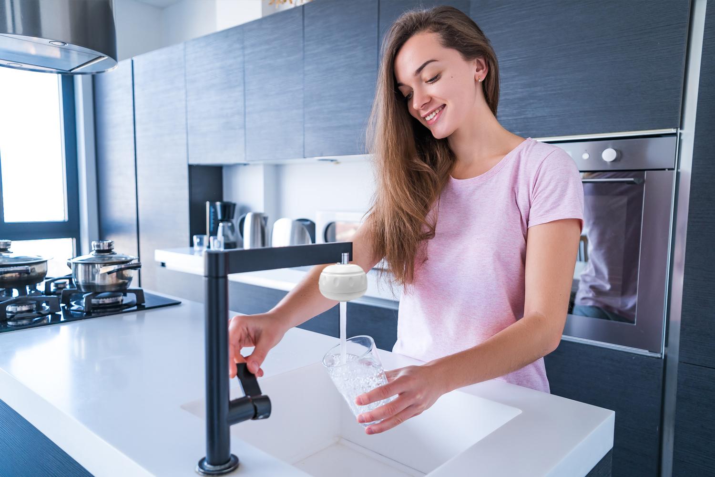 Eine Frau nutzt den Trinkwasserfilter am Wasserhahn