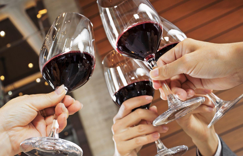 Drei Menschen stoßen mit Rotwein an.