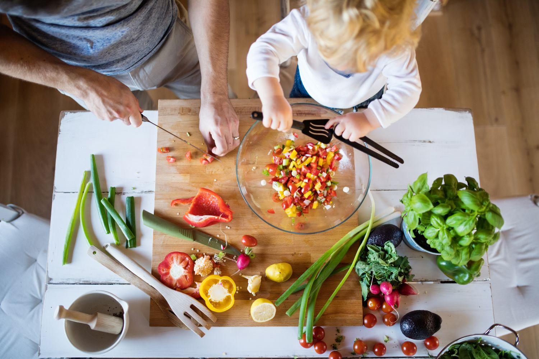 Ein Vater steht mit seinem Kind am Küchentisch und bereitet das Essen vor. Thema: Ausgewogene Ernährung