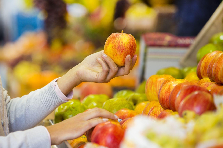 Frau am Obststand: Sie hält einen Apfel in der Hand.