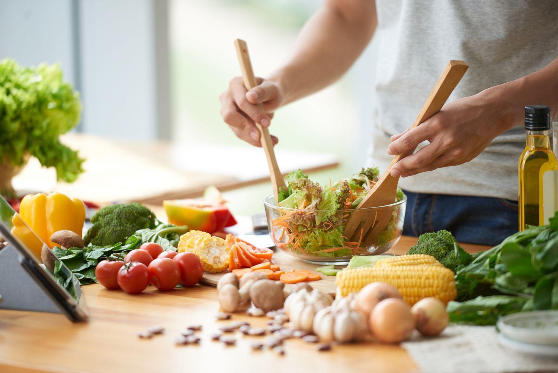 Zubereitung eines Salats; die Arbeitsfläche ist mit Gemüse eingedeckt. Thema: Vegane Proteinquellen