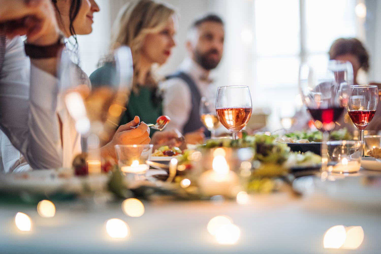 Detailansicht einer gedeckten Tafel, an der mehrere Personen sitzen und speisen.
