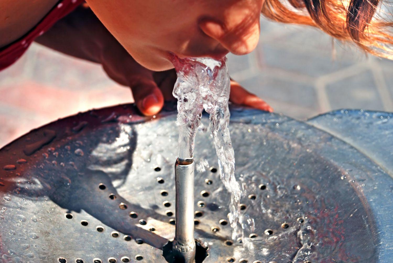 Person, die von einem Wasserspender trinkt.