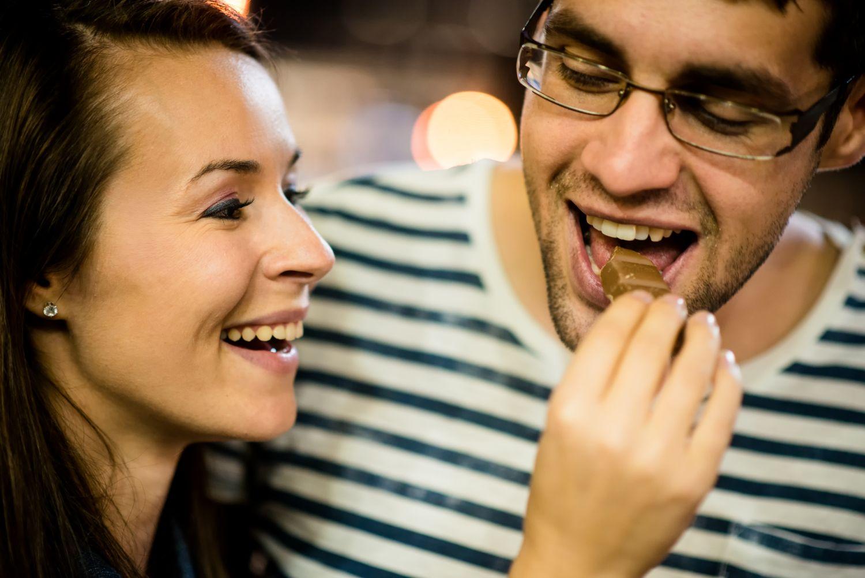 Pärchen füttert sich mit Schokolade. Thema: Vegane Süßigkeiten
